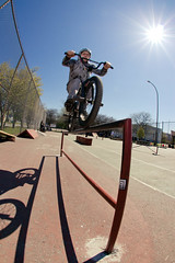 Korey Kryder with a tire ride up the round rail in the DIY tennis court park.