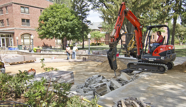 Workers remove the east steps of the Gizmo patio as the work in placing concrete pavers continue on Tuesday, July 10.