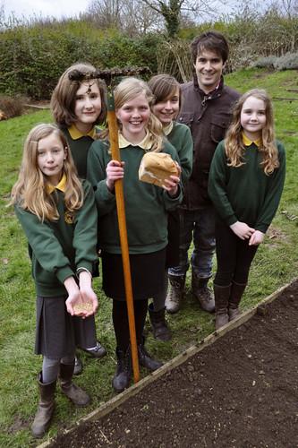 由麵包廚師明星Tom Herbert擔任真麵包大使,在英國西南部格洛斯特郡一所學校教孩童種植小麥。此為Bake Your Lawn(試譯:從你家草地烤起)計畫活動之一。圖片來源:Real Bread Campaign