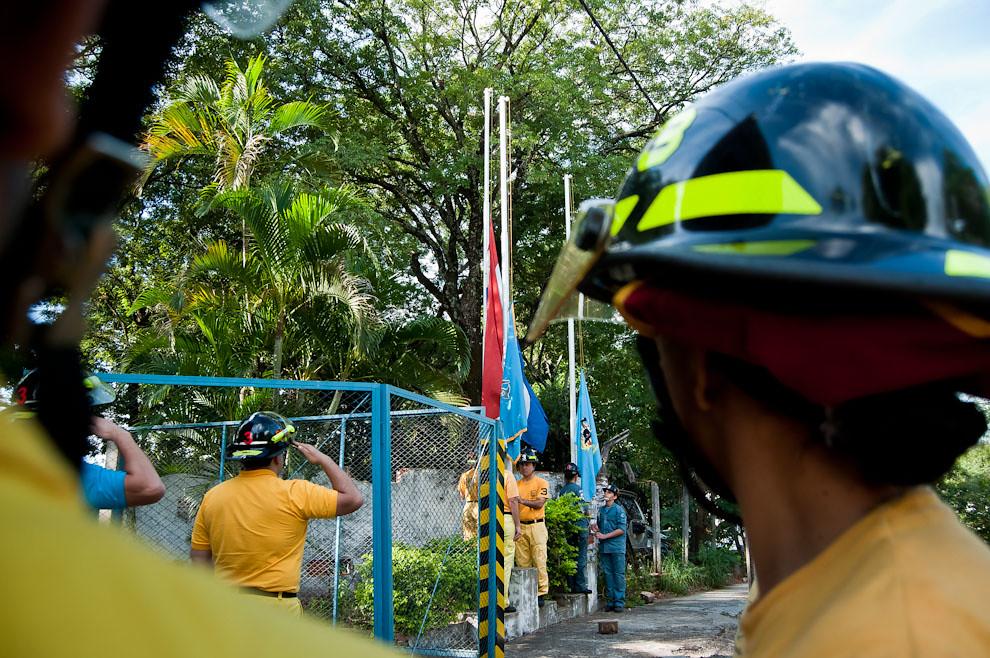El capitán de la 3ra. Compañía de Sajonia  saluda a la bandera paraguaya y la de la institución durante su izamiento el 12 de mayo antes de comenzar la jornada de prácticas. Así también lo hacen los bomberos voluntarios combatientes poniéndose firmes y con la mirada fija hacia el pabellón patrio. (Elton Núñez)