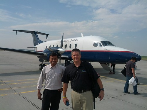 Sazzad and Jeff smiling front of a small plane.