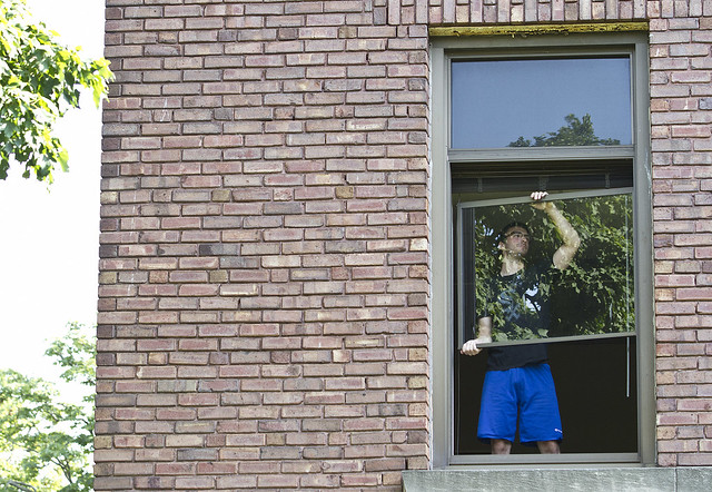 Student works clean windows on the second floor of GDH on July 5.