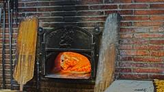 masonry oven(1.0), wood(1.0), wood-burning stove(1.0), fireplace(1.0), iron(1.0), brickwork(1.0), hearth(1.0),