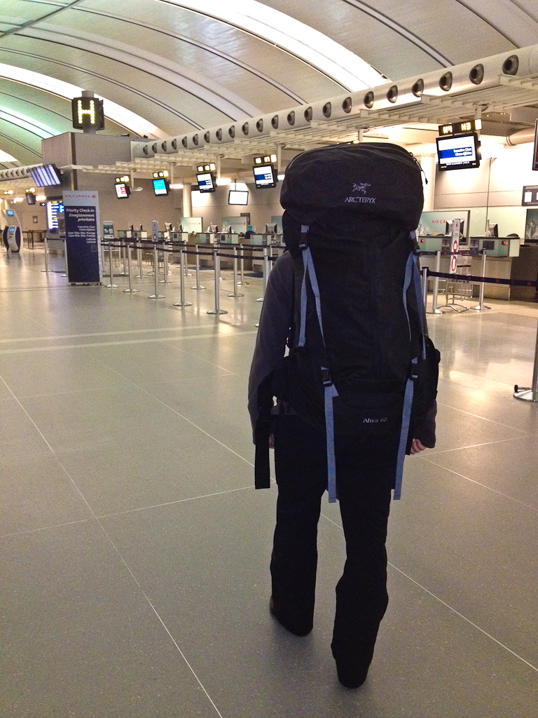Deb of Adventure Couple traveling at airport with backpack