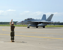 An Electronic Attack Squadron (VAQ) 132 crew member directs an EA-18G Growler as it taxis down the Naval Air Facility Misawa ramp, July 14. (U.S. Navy photo by Senior Chief Mass Communication Specialist Daniel Sanford)