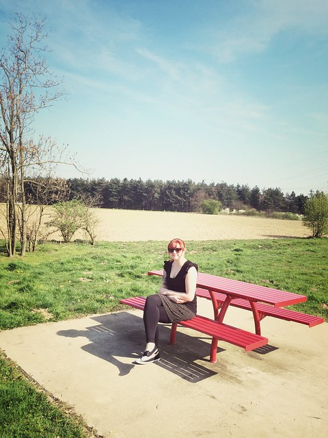 The red haired girl on the red bench