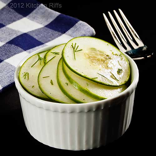 Hungarian Cucumber Salad in White Ramekin with Napkin and Fork, Black Background