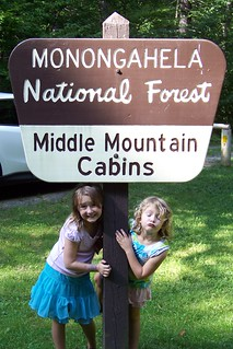 Middle Mountain Cabins sign with girls 1