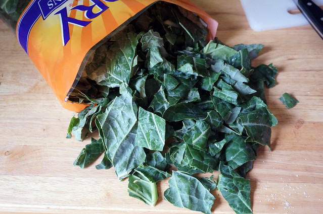 Chopped collards, dark green and shiny, spill out of a bright orange plastic bag onto a wooden counterop: pre-chopped greens are my lazy friends