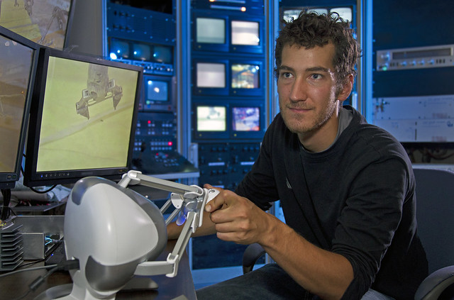 Los Alamos National Laboratory graduate student Matt Brown uses a 3D haptic controller, used for video games, to operate a robot arm for handling radioactive material at the Los Alamos Neutron Science Center.