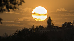 Sunset behind Buddha state of Wat Phra That Doi Kham, Buddhist temple in the historic of Chiang Mai, Thailand.