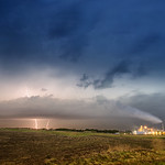 12. Mai 2014 - 1:28 - Lightning strikes through a cloud created by a factory in Nebraska. Lightning is a sudden electrostatic discharge during an electrical storm between electrically charged regions of a cloud (called intra-cloud lightning or IC), between that cloud and another cloud (CC lightning), or between a cloud and the ground (CG lightning). The charged regions in the atmosphere temporarily equalize themselves through this discharge referred to as a strike if it hits an object on the ground, and a flash if it occurs within a cloud. Lightning causes light in the form of plasma, and sound in the form of thunder. Lightning may be seen and not heard when it occurs at a distance too great for the sound to carry as far as the light from the strike or flash.