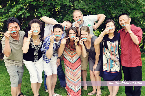 gender reveal party: they think it's a boy so they held up paper mustaches