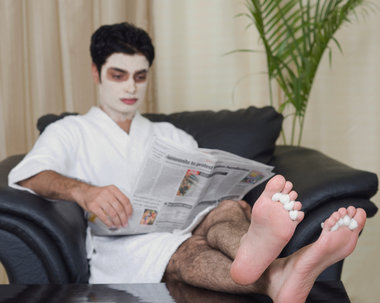 a white man with a face mask getting a pedicure