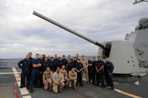 Sailors and Marines assigned to USS Mustin (DDG 89) and 3rd Marine Expeditionary Force pose for a photo on Mustin's forecastle