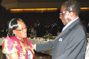 President Mugabe chats with Politburo member Cde Tsitsi Muzenda before the Zanu-PF Central Committee meeting in Harare on March 30, 2012. Mugabe says that elections will be held this year in the Southern African state. by Pan-African News Wire File Photos