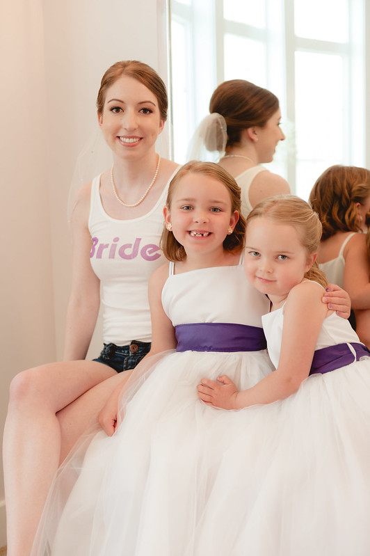 A bride and her flower girls pose for a photo while getting ready for the wedding