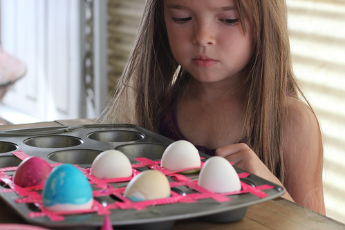 colored eggs in a muffin tin