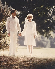 screen shot from the Great Gatsby movie showing a couple dressed all in white walking on a road