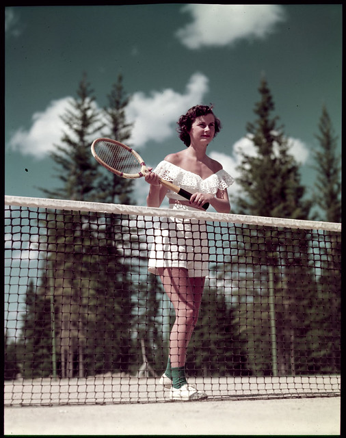 woman holding tennis racquet behind tennis net une femme. Black Bedroom Furniture Sets. Home Design Ideas