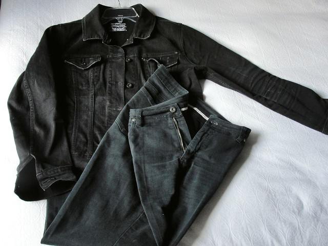 A faded black denim Levi's jacket and faded black jeans laid out on a white background