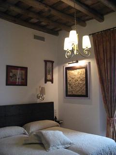 Aspecto de una de las coquetas habitaciones de La Posada del Infante, visionando la antigua pared enmarcada como un cuadro.