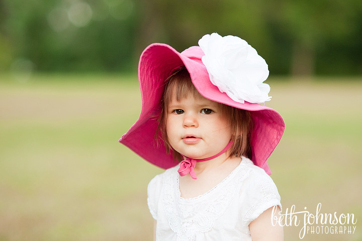 baby girl in pink floppy hat at maclay gardens open field