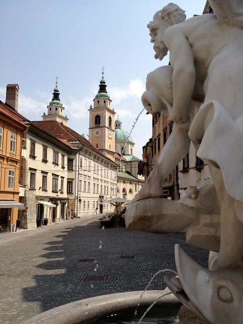 A view of St. Nicholas Cathedral past a statue in Ljubljana