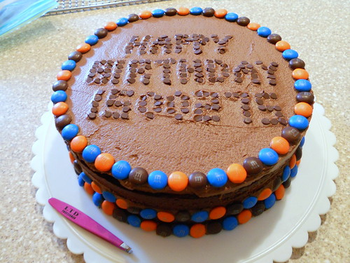 chocolate cake decorated with candy around the edges and text written in mini M&Ms. Text reads Happy Birthday 1500275