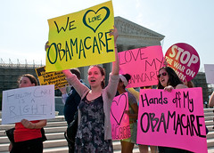 women with pro-Obamacare posters outside the Supreme Court