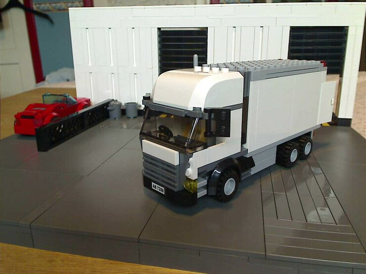 Small lorry in yard outside a LEGO® model of a warehouse