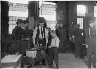 Teaching the young idea. The boss (who began at 10 years of age, and has been at it for 30 years) showing a beginner (who is apparently 9 or 10), October 1908