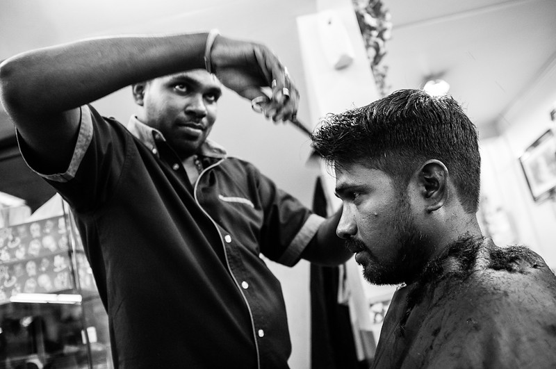 Barber cutting the hair of his customer at Little India. Where in Singapore can you walk into a barber shop and take photos of the activity inside? Only in Little India.
