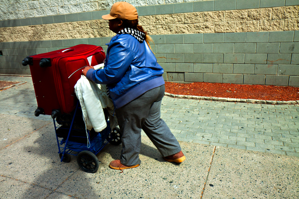 Woman-pushing-cart-with-suitcase-on-top-outside-Greyhound-on-4-13-14--Center-City