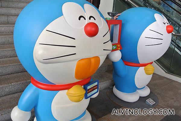 Two Doraemons beside the escalator