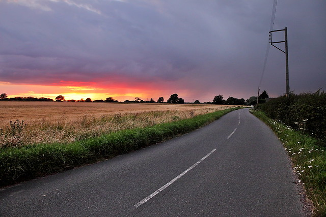 Sunset through storm clouds over a road in Essex, with bright purple, orange and yellow colours. Road and fields near the Essex Lion.