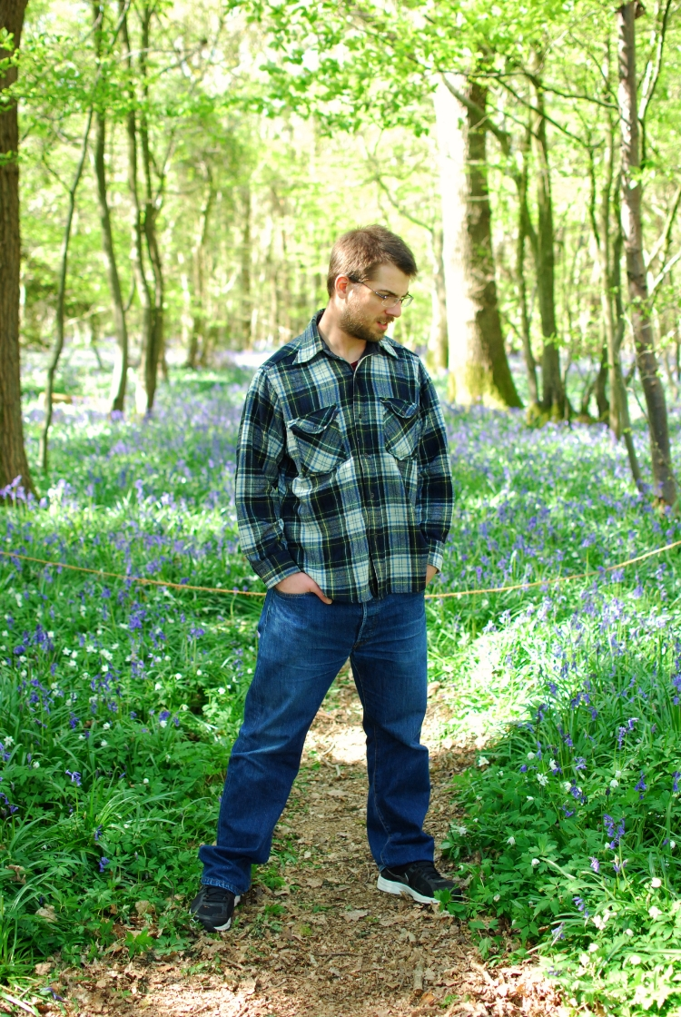 chambray and curls standing mong the bluebells