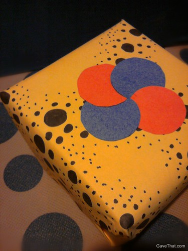 Simple dots form a pin wheel embellishment on the top of gifts in this easy DIY gift wrapping look