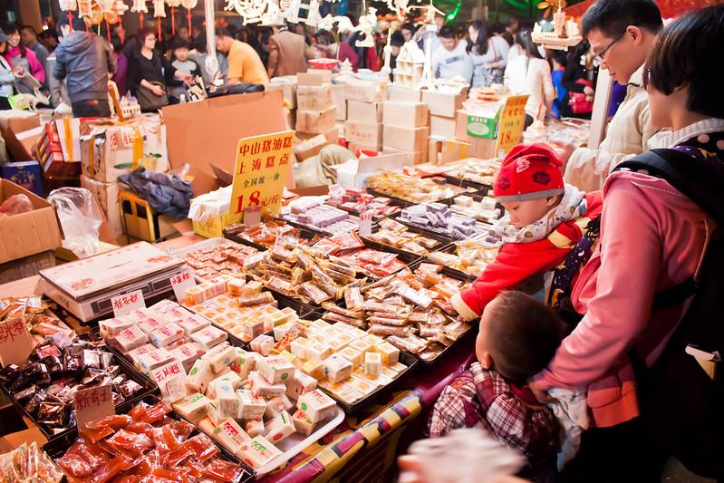 Un niño cogiendo dulces en un puesto del mercadillo de Año Nuevo chino de Guangzhou.