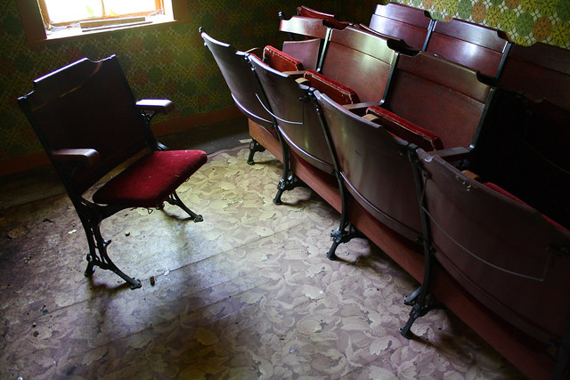 The beautiful old theatre seats with detailed cast iron legs, cherry backrests and arms, and red velvet padded seats.