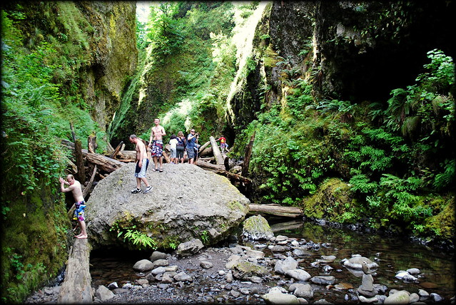 Hikers coming over the log jam at Oneonta Gorge