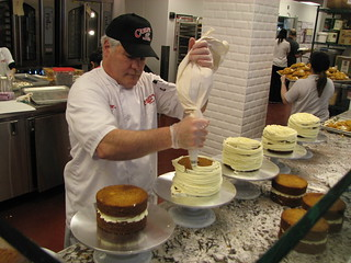 Carlo's Bakery employee frosts cakes