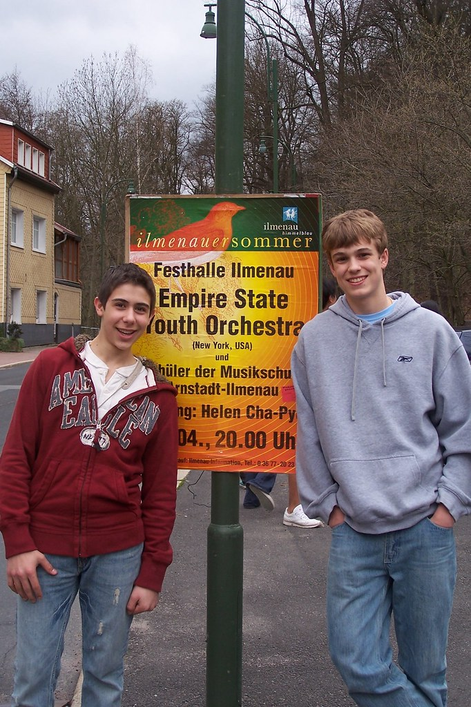 Empire State Youth Orchestra members pose in front of one of their concert promotion posters in Ilmenau