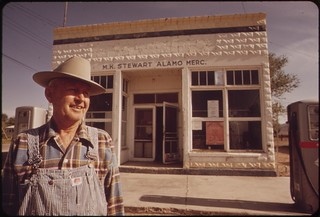 Owner in front of his general store in Alamo. M.K. Stewart is one of several citizens who wears a TLD (thermo-luminescent docimeter) to measure radioactive fallout. EPA provides and monitors the TLD capsules, May 1972