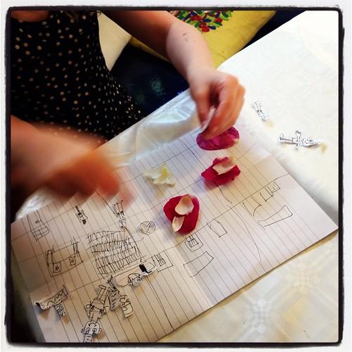 Klara berättar saga med rosenblad och urklippta Smurfar medan jag diskar