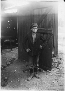 A glass works boy waiting for the night shift. Indiana, August 1908
