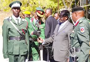 President Mugabe hands over a sword to Army Commander Lieutenant General Phillip Valerio Sibanda for the best student, Wishes Manenji (left), at the Zimbabwe Military Academy in Gweru on July 12, 2012. by Pan-African News Wire File Photos