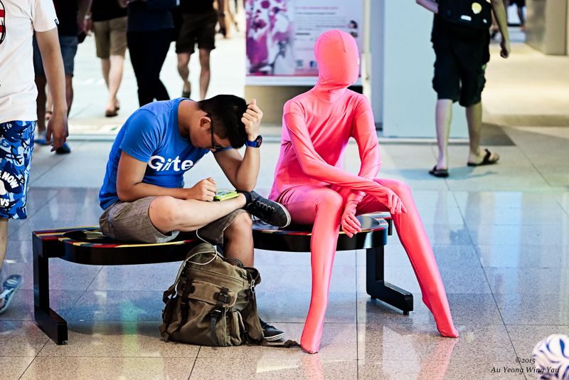 Man Sitting Beside Colouful Mannequin In Urban Mall