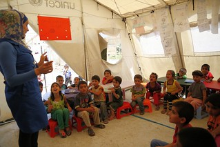 Syrian refugee children attend a lesson in a UNICEF temporary classroom in northern Lebanon, July 2014