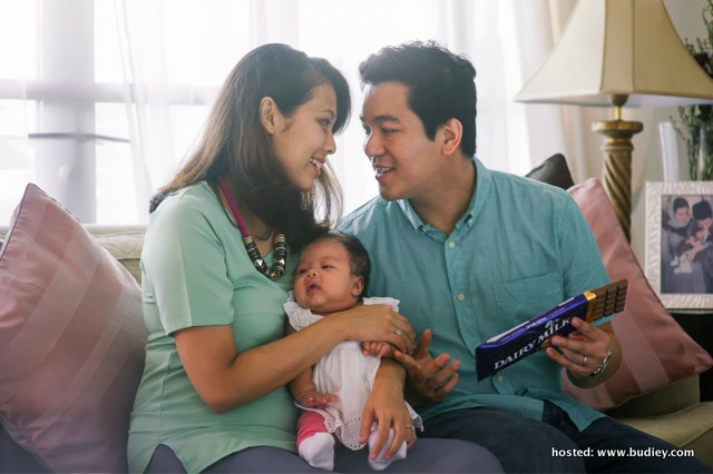 Ben looks happy as he discovers the secret message printed on the Cadbury Dairy Milk bar while Sofia holds Kyla.